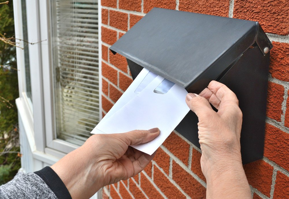 person getting mail from mailbox